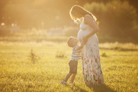 Small boy kissing belly of his pregnant mother outdoors photo