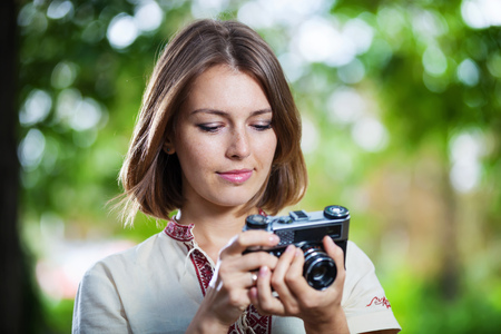 20s  closeup: Young woman looking at screen of retro style camera and smiling