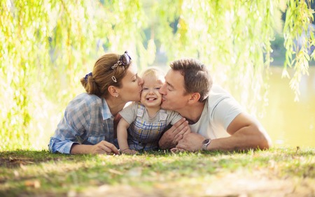 child couple: Happy parents kissing toddler boy. Father, mother and son relaxing on the lawn.