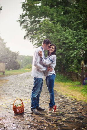 Young couple in Ukrainian style clothes standing under rain photo