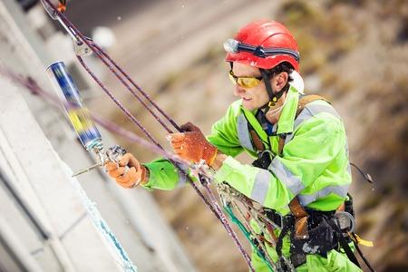 Industriële klimmer op een gebouw tijdens winterklaar werken Stockfoto