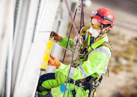 Industrial climber measuring with level tube during winterization works
