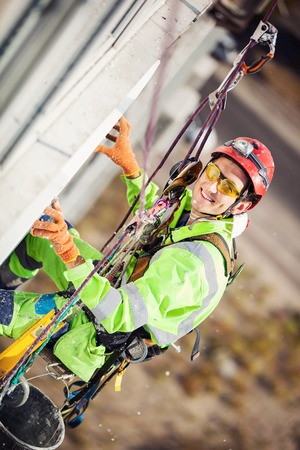Industrial climber placing a polyfoam sheet insulation to a wall of a building