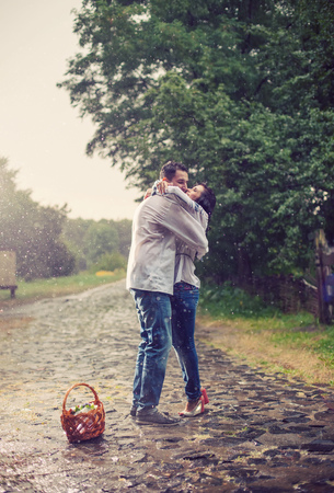 Young couple in Ukrainian style clothes kissing while standing under rain photo