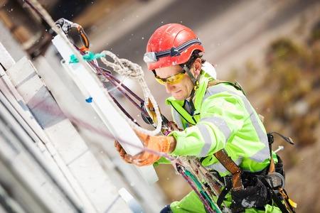 klimmer: Industriële klimmer het plaatsen van een polyfoam vel isolatie om een muur van het gebouw
