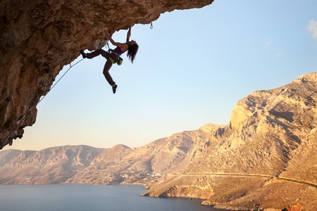 one female: Silhouette of a young female rock climber on a cliff. Kalymnos Island, Greece