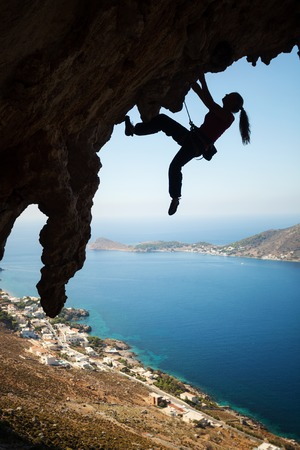 lead rope: Silhouette of a young female rock climber on a cliff. Kalymnos Island, Greece