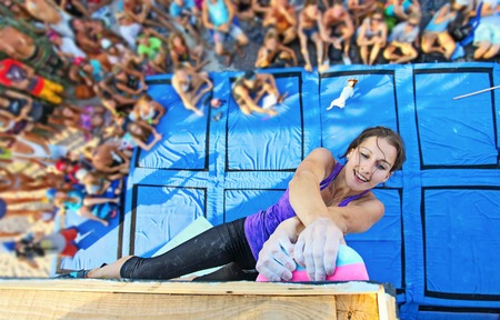 handhold: Female climber participating in rock climbing competition, gripping top handhold