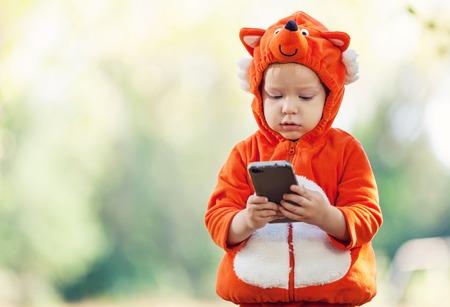 Joyful bambino ragazzo in volpe smartphone costume azienda