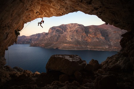 Silhouette of a female rock climber on a cliff in a cave at Kalymnos, Greece