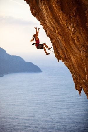 Female rock climber falling of a cliff while lead climbing Imagens