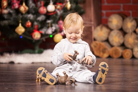 christmas baby: Cheerful little boy playing with his toy animals by Christmas tree