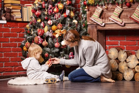 Mother and toddler son holding Christmas ball on Christmas tree at home photo