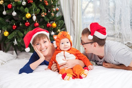 Young family with baby boy dressed in little fox costume photo