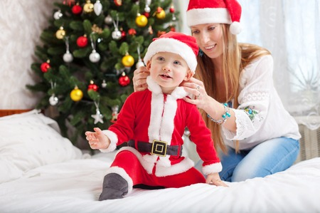 Happy mother putting Santa costume on toddler son at home photo