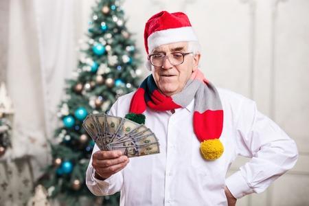 hold ups: Senior man with money on Christmas background
