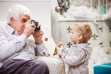 grand kid: Senior man taking photo of his toddler grandson at Christmas time