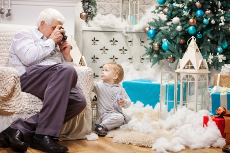 2 year old: Senior man taking photo of his toddler grandson while sitting near Christmas tree at home