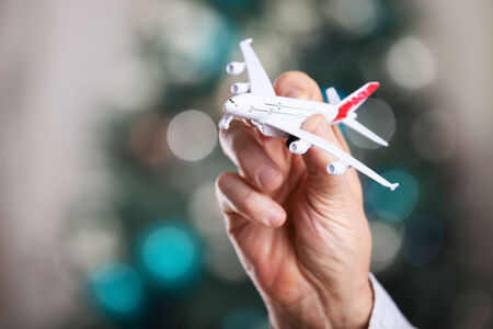 model airplane: Closeup of man hand holding model of airplane on a Christmas background