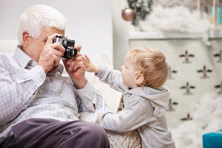 Senior man taking photo of his toddler grandson at Christmas time