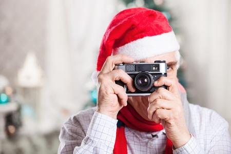 elder tree: Senior man taking photo on Christmas background