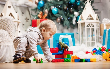 blocks: Cute toddler boy playing with building blocks at Christmas tree