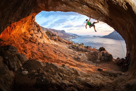 lead rope: Male rock climber climbing along a roof in a cave at sunset