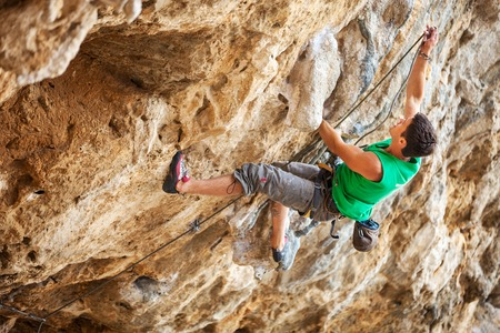Male rock climber on a face of a cliff photo