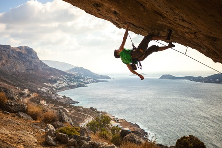 climber: Male climber climbing overhanging rock against beautiful view of coast below
