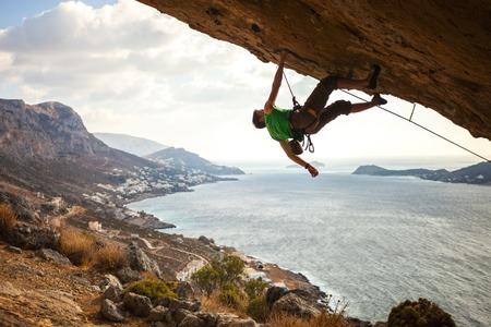 climber: Mannelijke klimmer klimmen overhangende rots tegen prachtig uitzicht op de kust hieronder