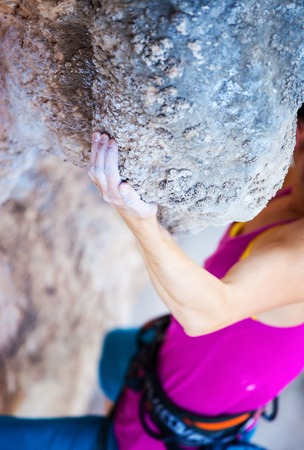 Magnesium: Cropped view of young woman climbing natural cliff, hand in focus Stock Photo