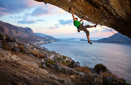 Male climber climbing overhanging rock against beautiful view of coast below