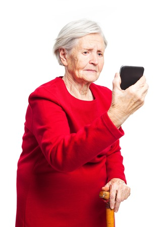 taking video: Upset elderly woman using touch screen mobile for taking selfie or making video call