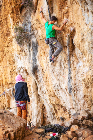 rockclimber: Young man lead climbing on natural cliff, belayer watching him