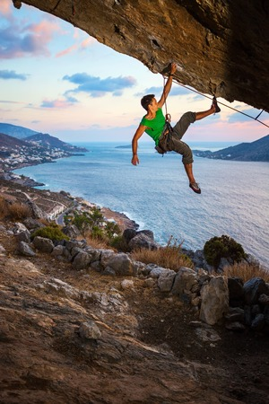 hanging on: Male rock climber climbing along a roof in a cave at sunset
