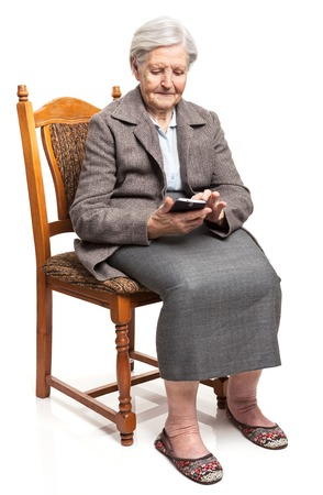 Senior woman using mobile phone while sitting on chair Banque d'images