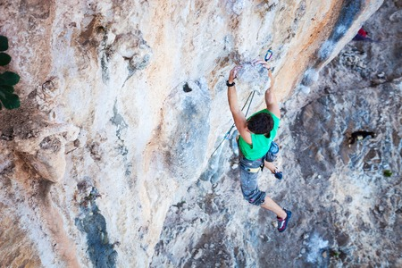 lead rope: Rock climber holding on handhold while climbing cliff