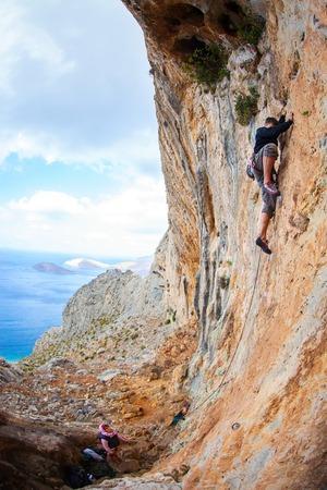 lead rope: Young man lead climbing on cliff near sea, Kalymnos island, Greece Stock Photo