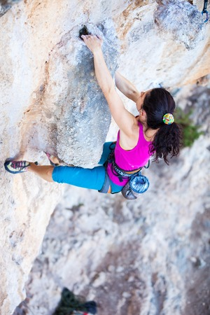 Young female rock climber on a cliff face photo