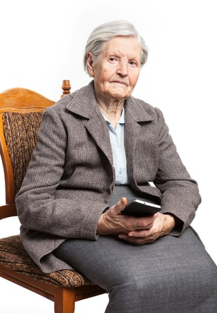 senior business: Senior woman sitting on chair and holding mobile phone Stock Photo