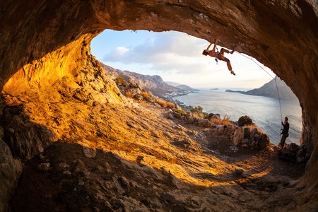 Young woman lead climbing in cave with beautiful view in background Foto de archivo
