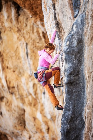cliff face: Young female rock climber on a cliff face