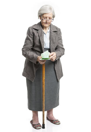 old people walking: Senior woman counting money while standing over white background