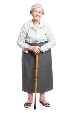 Senior woman with walking stick standing over white Foto de archivo