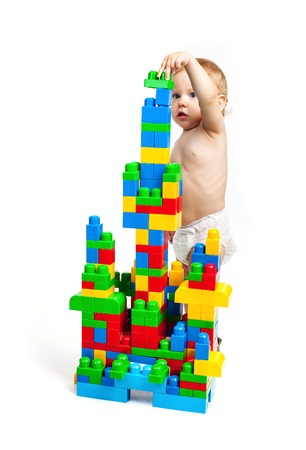 Toddler boy is playing with building blocks over white background photo