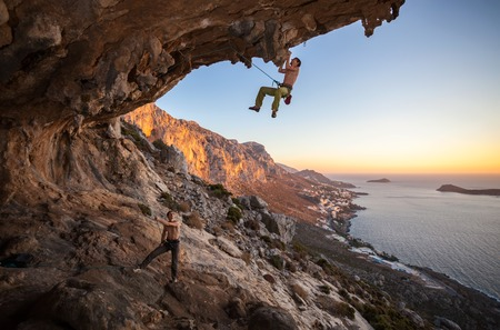 belaying: Male rock climber climbing on a roof in a cave, his partner belaying