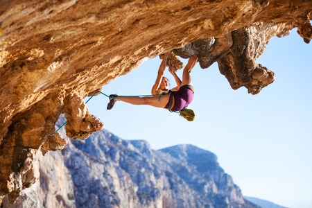rock climb: Young female rock climber on a cliff face