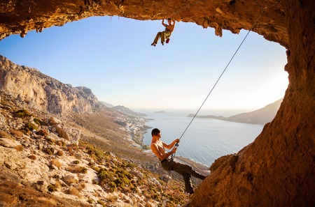 lead rope: Male rock climber climbing on a roof in a cave, his partner belaying