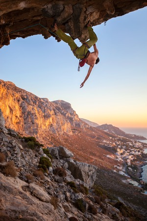 overhanging: Male climber on overhanging rock against beautiful view of coast below