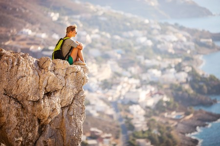 cliff edge: Young woman sitting on rock and enjoying beautiful view